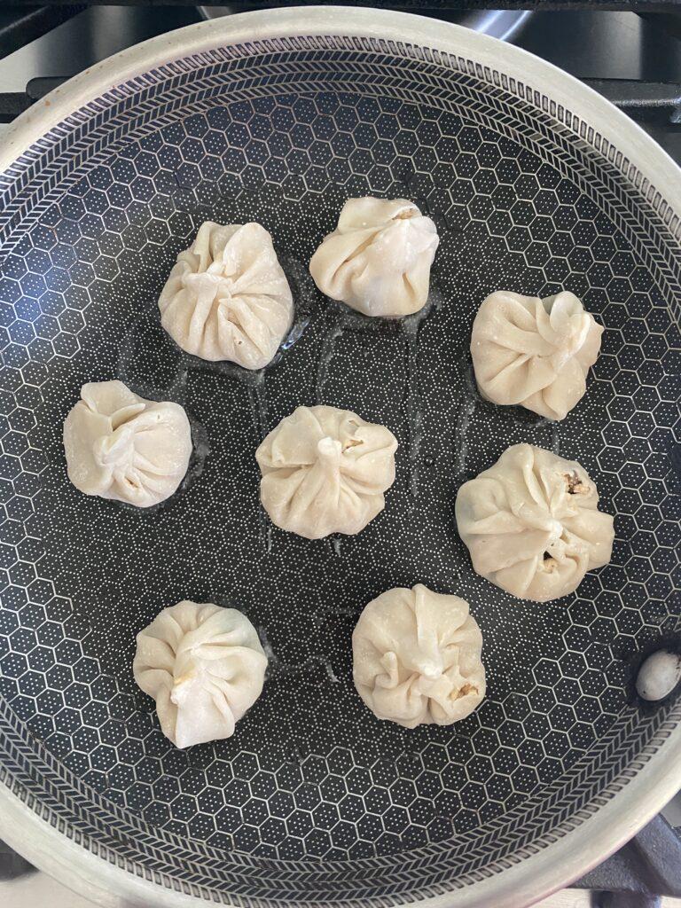 cooking dumplings in a pan with oil