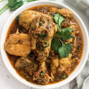 indian chicken curry cooked in a tapelu plated on a white dish with cilantro
