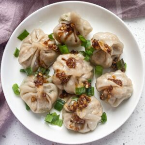 vegan momos in a place with scallions and red chili oil over it