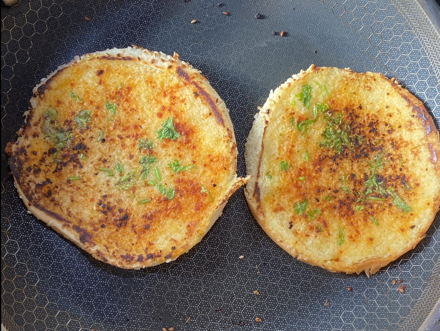 grilled burger bread in a pan with butter, red chili powder, cilantro