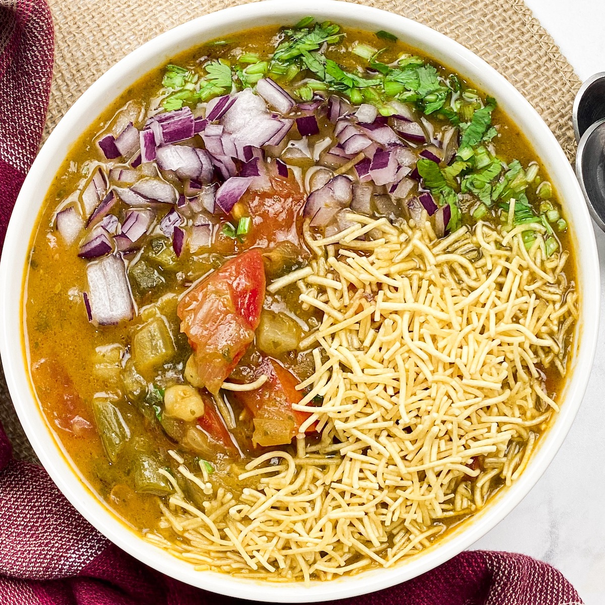 sev usal in a bowl with onions, tomatoes, cilantro, and soup